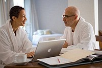 Mature woman working on a laptop and looking at a mature man sitting beside her