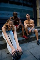 Young woman touching her toes with two men talking to each other behind her