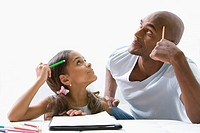 Mixed race father helping daughter with homework