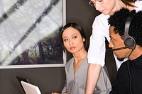 Young Asian businesswoman looking at African man in office