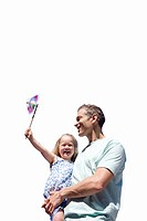 Father holding daughter with pinwheel, smiling, cut out (thumbnail)