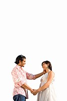 Young couple holding hands, smiling at each other, cut out (thumbnail)