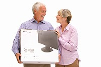 Senior couple holding new television in box, cut out (thumbnail)