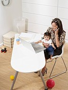 Hispanic working mother and baby son in home office