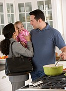 Hispanic businesswoman greeting family in kitchen