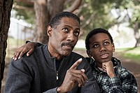African man talking with son in park