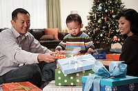 Asian family with gifts next to Christmas tree