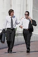 Hispanic businessman talking on cell phone and walking with co_worker