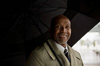 African businessman holding umbrella