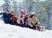 Children riding downhill on sled