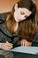 Young woman signing document