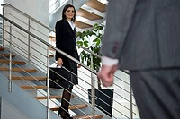 Businessman walking up to businesswoman on staircase (thumbnail)