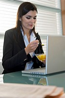 Professional woman eating fruit salad over laptop
