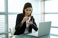 Professional woman with nail polish at desk with laptop