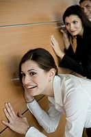 Office workers eavesdropping against wall (thumbnail)