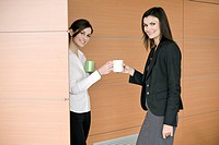 Businesswoman bringing coffee to another businesswoman (thumbnail)