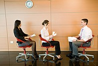 Office workers sitting in chairs with documents (thumbnail)