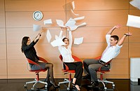 Office workers throwing documents up in the air (thumbnail)