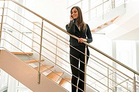 Businesswoman talking on cell phone on office staircase (thumbnail)