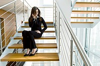 Businesswoman talking on cell phone on office staircase