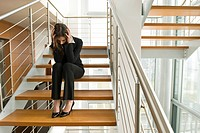 Businesswoman on office staircase holding her head