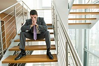 Businessman on office staircase with face in hands