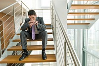 Businessman on office staircase with head on hands