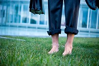 Businessman's bare feet on grass outside of office building