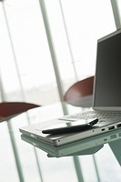 Laptop with cell phone on conference table