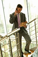 Businessman with financial newspaper on staircase talking on cell phone