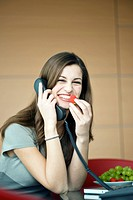 Businesswoman eating a strawberry on telephone
