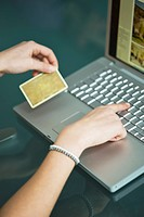 Businesswoman's hands holding credit card at laptop