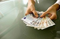 Woman's hands holding euro bills