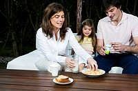 Young couple and girl having breakfast outdoors
