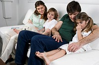 Young couple on couch with children and dog