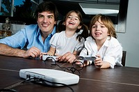 Young man with children playing video game