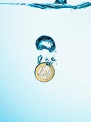 Euro coin dropping into water