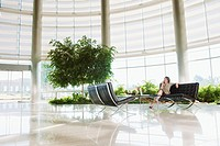 Businesswoman using cell phone in atrium
