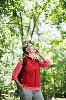 Woman Using Cell Phone in Woods