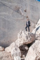 businessman standing on rock in quarry