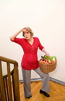 exhausted pregnant woman carrying basket
