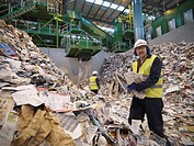 Workers With Paper In Recycle Plant