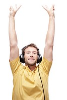 Young man wearing headphones, hands up, portrait