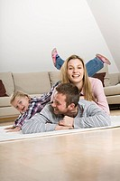 Parents and daughter 3_4 at home, lying on floor, fooling about