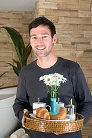 Young man carrying tray with breakfast, smiling, portrait
