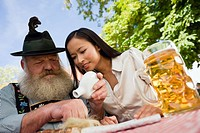 Germany, Bavaria, Upper Bavaria, Bavarian man and Asian woman in beer garden, Bavarian man sniffing snuff