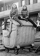 Seventies, black and white photo, people, children, two girls sitting on a refuse container, street kids, aged 10 to 13 years