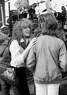 Seventies, black and white photo, people, two young girls talking during a pop concert, blouse, jacket, trousers, aged 18 to 22 years