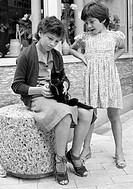 Seventies, black and white photo, people, children, two young girls with a black cat, aged 11 to 13 years, aged 6 to 8 years, France, Loire Valley