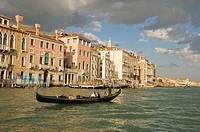 Italy, Venice.  Gondolier takes tourists on a gondola tour of the grand canal